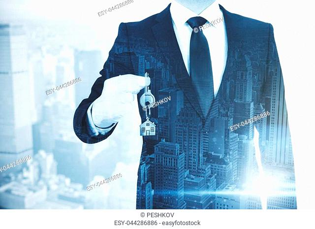 Businessman holding key with house keychain on abstract city background. Real estate and housing concept. Double exposure