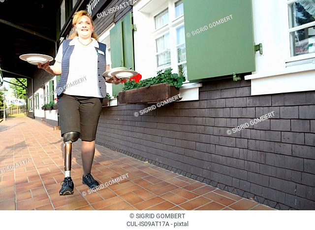 Mid adult woman with prosthetic leg, carrying plates, outdoors