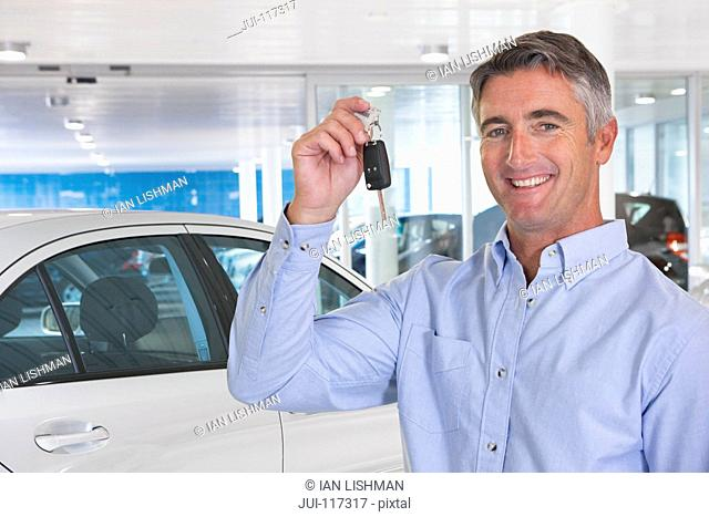 Portrait Of Man Collecting New Car From Showroom