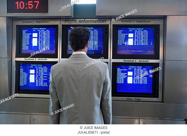 Businessman looking at Arrivals screen