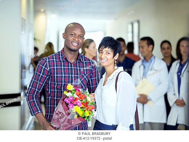 Couple carrying bouquet of flowers in hospital