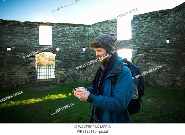 Male hiker using mobile phone in old ruin at countryside