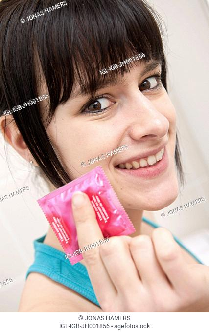 This picture shows a young caucasian woman with brown hair as she stands in her bathroom with a condom in her hand