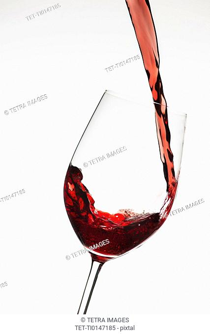 Close up of red wine being poured into glass on white background