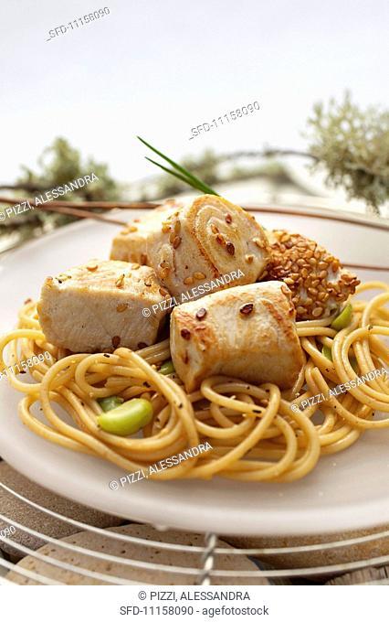 Bocconcini di tonno (bite-sized chunks of tuna, Italy) with sesame seeds, on spaghetti