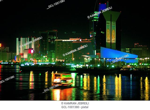 Dhow crossing the creek in Dubai at night, UAE