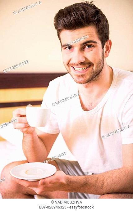 Young smiling male is drinking morning coffee in hotel room