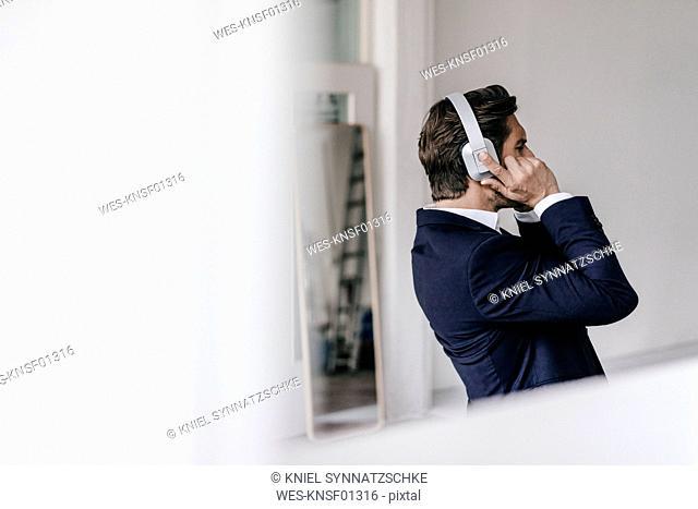 Businessman listening to music on headphones