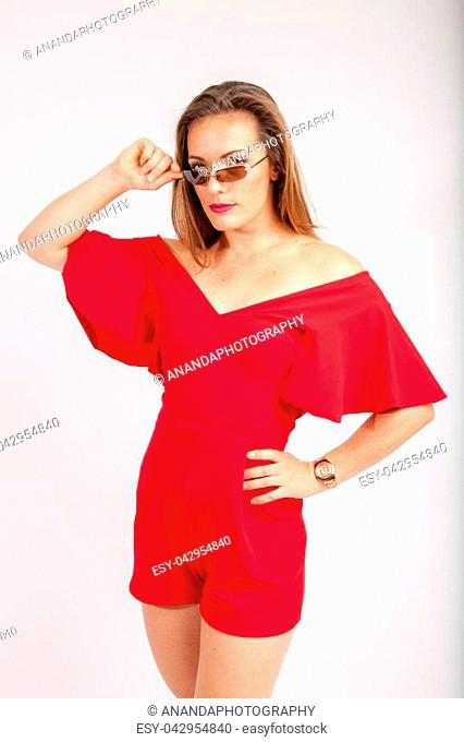 beautiful women in red dress with one hand in her hip looking over her glasses