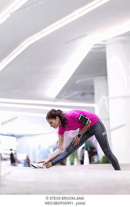 Young woman in pink sportshirt listening to music and stretching in front of modern building