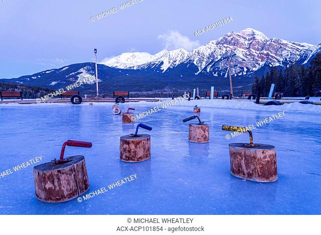 Wooden curling rocks, await at Pyramid Lake in winter, Jasper National Park, Alberta, Canada