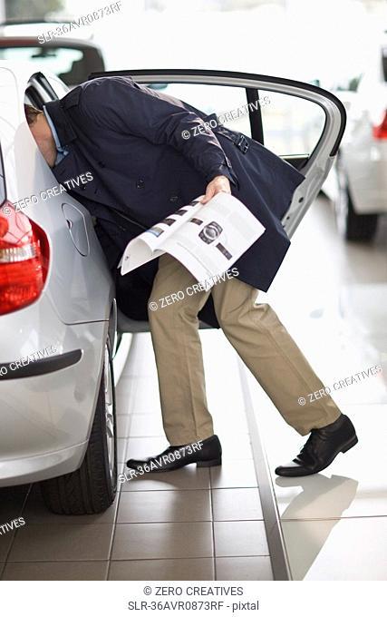 Customer examining car in showroom