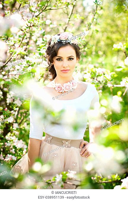 Portrait of beautiful girl posing outdoor with flowers of the cherry trees in blossom during a bright spring day. Attractive brunette woman with flowers...