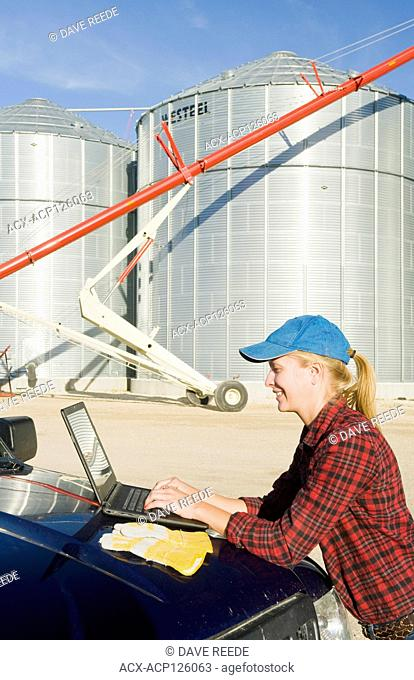 girl using a computer next grain bins in a farmyard, near Lorette, Manitoba