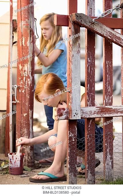 Caucasian girls painting fence