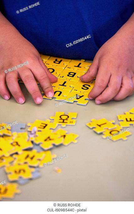 Hands of preschool boy doing jigsaw alphabet in classroom