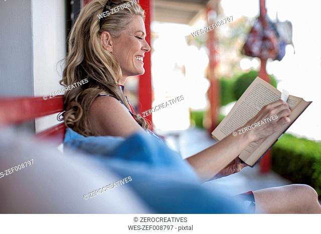Woman reading a book, terrace