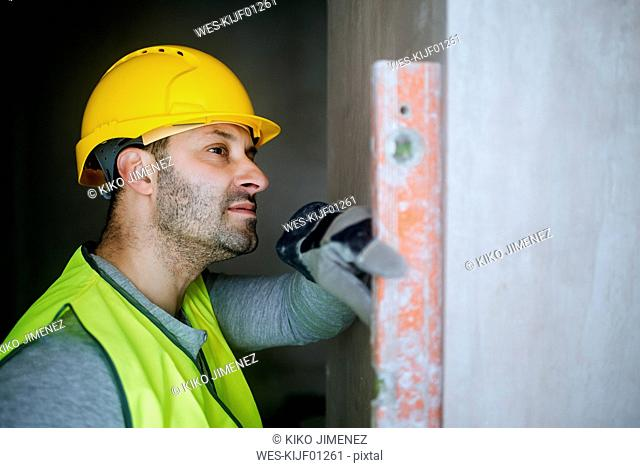 Construction worker using a water level on a wall