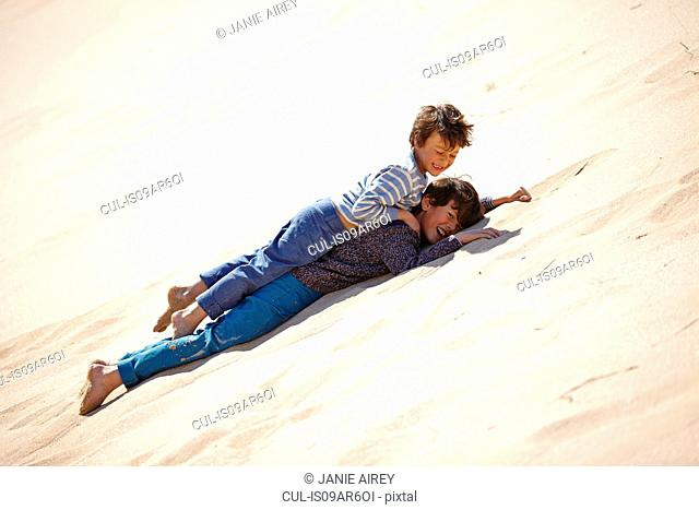 Two young boys lying on sandy hill, playing