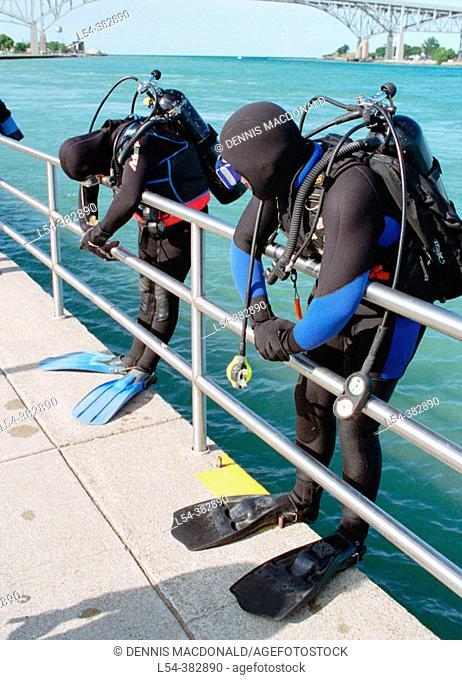Scuba divers prepare to enter water into St. Clair River to explore old shipwrecks. Michigan, USA