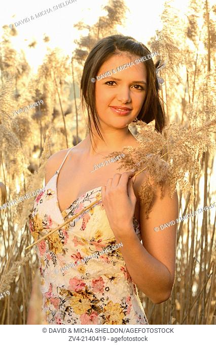 Half-length Portrait of a good looking young woman in the reeds at sunset in early spring