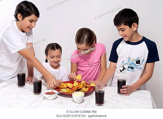 Two boys and two girls eating nachos from a platter