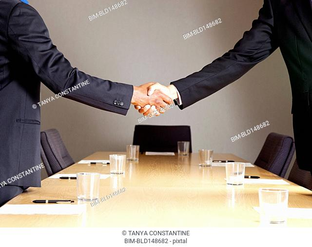 Mixed race businessmen shaking hands in conference room