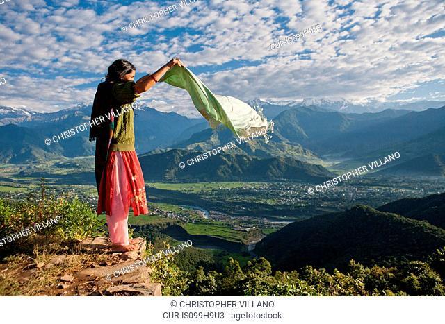 Nepalese woman holding scarf on cliff edge near Pokhara, Nepal