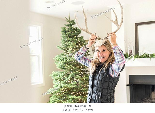 Caucasian woman holding antlers to head near Christmas tree