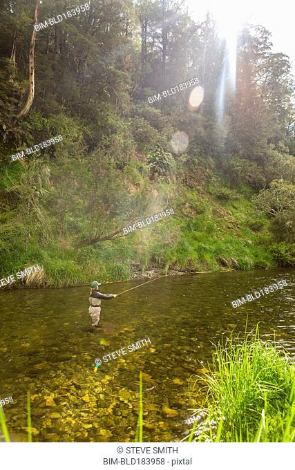 Caucasian woman fishing in remote river