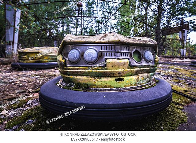 Yellow bumper car in amusement park of Pripyat ghost city, Chernobyl Nuclear Power Plant Zone of Alienation around nuclear reactor disaster, Ukraine