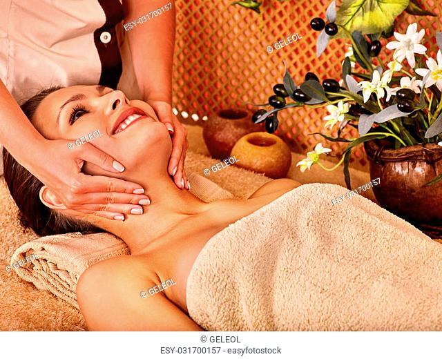 Woman getting head massage in tropical beauty spa. A lot of flower