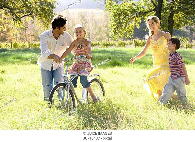 Family of four in field, father helping daughter 5-7 on bicycle, smiling