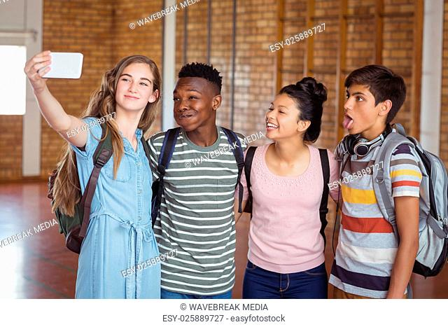 Happy students taking selfie on mobile phone in campus