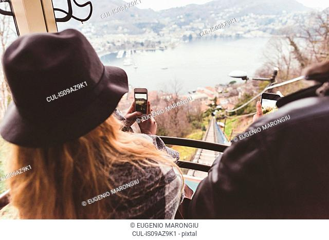 Over the shoulder view of couple on funicular photographing Lake Como, Italy