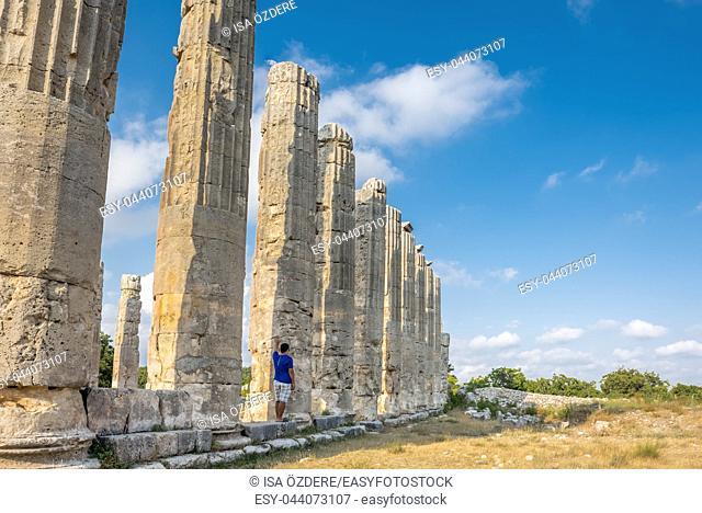 Young man in t-shirt, outdoor laying marble columns at Zeus temple at Uzuncaburc Ancient city located in Uzuncaburc,Silifke,Mersin,Turkey