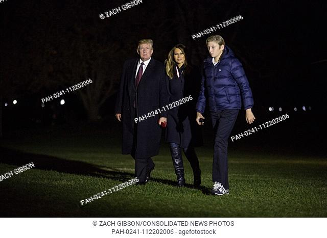 President Donald Trump crosses the South Lawn with First Lady Melania Trump and his son, Barron Trump, after returning to the White House from a Thanksgiving...