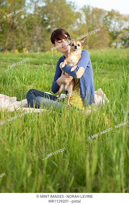 A young woman sitting in an open space, a grass field, on a blanket, holding a small Chihuahua dog