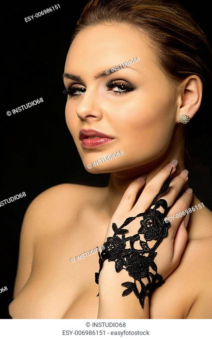Closeup head and shoulders studio portrait of an exotic beauty with sultry eyes and bare shoulders posing with her hand in a black lace glove raised to her neck