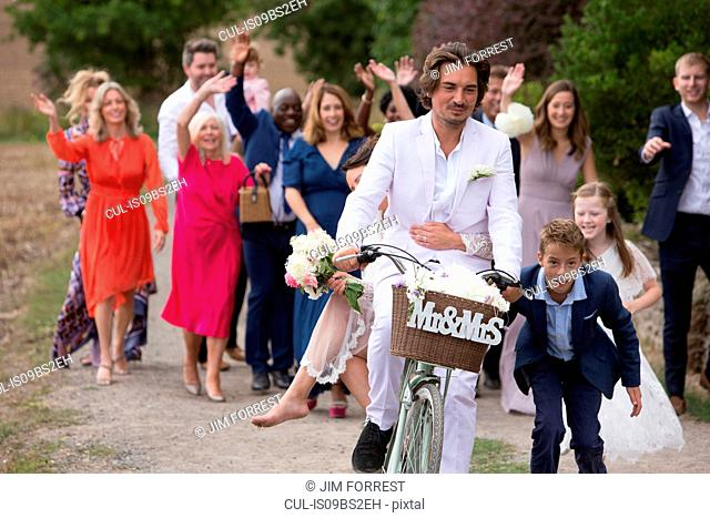 Wedding guests waving off newlyweds on bicycles