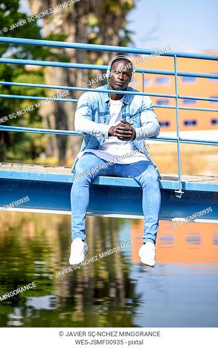 Portrait of man wearing casual denim clothes sitting on footbridge listening music with wireless headphones