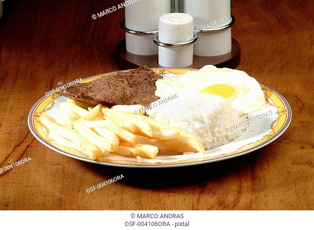 fried egg rice french fries and steak food dish
