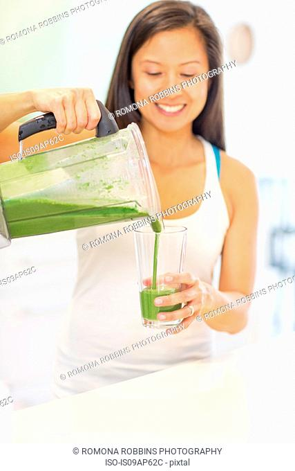 Mid adult woman pouring green smoothie in kitchen