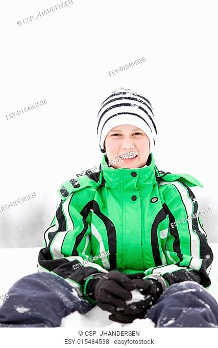 Young boy kneeling in the snow making snowballs