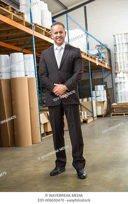 Smiling warehouse manager standing with hands together