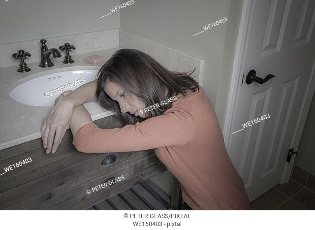 Young woman kneeling by her bathroom sink