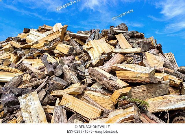 Big heap of chopped tree trunks for heating season in winter