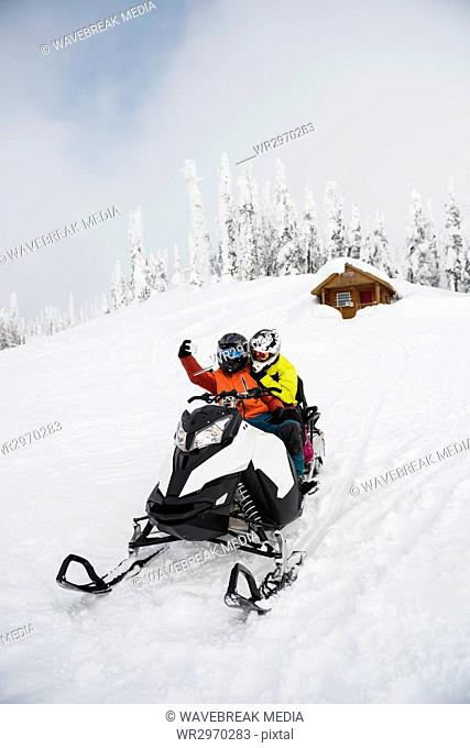 Couple taking selfie on mobile phone while riding snowmobile