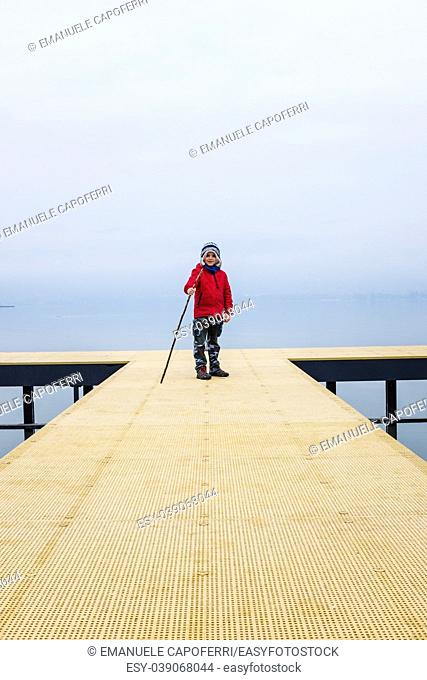 child over a wooden jetty extending over the water on a winter day with fog