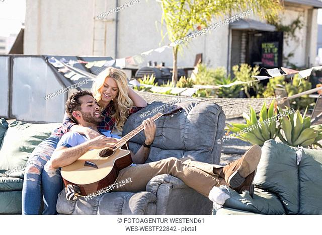 Couple on rooptop sitting on sofa and playing guitar